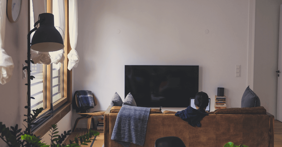 Woman sitting in her apartment, in the living room, in front of the TV. Featured image for blog post.