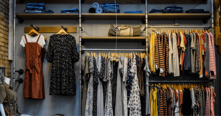 A wardrobe with a lot of colorful and different designed clothes.